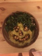 Pumpkin cornmeal porridge with roasted seeds, peanuts, and greens
